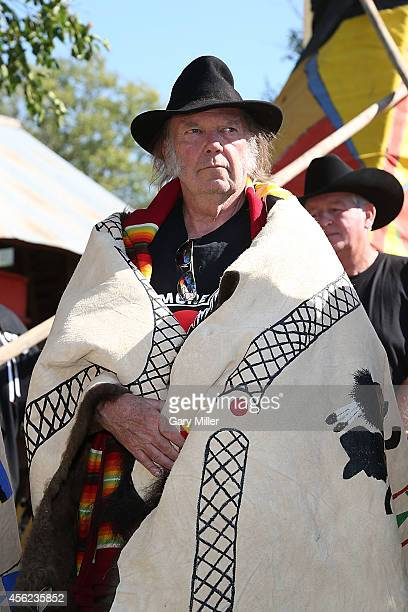 Neil Young is honored during a ceremony where he and Willie Nelson were presented with decorated buffalo hides before the Harvest The Hope Concert in...