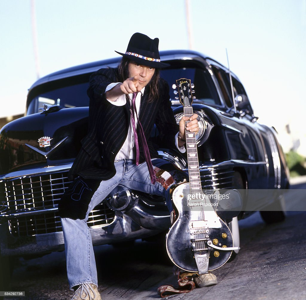 Neil Young sitting on bumper on 1950s Cadillac