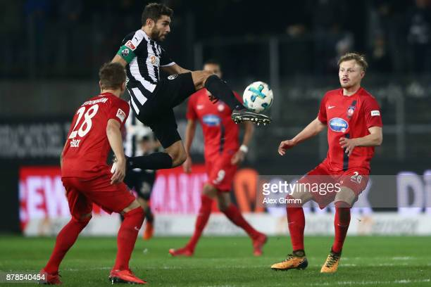 Nejmeddin Daghfous of Sandhausen controls the ball ahead of Arne Feick and Marcel TitschRivero of Heidenheim during the Second Bundesliga match...