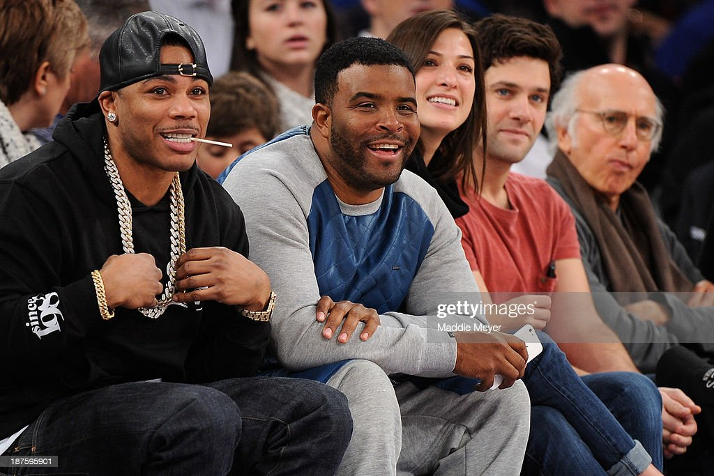 Nelly (L) watches the game between the New York Knicks and the San Antonio Spurs at Madison Square Garden on November 10, 2013 in New York City. The Spurs defeat the Knicks 120-89.