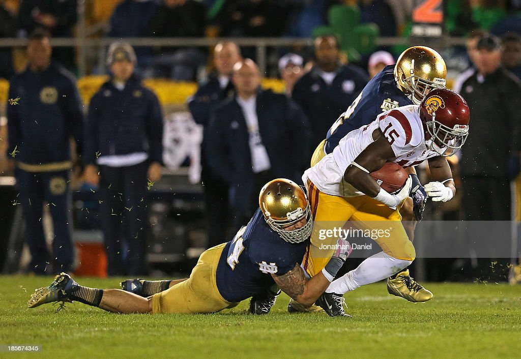 Nelson Agholor #15 of the University of Southern California Trojans is tackled by Carlo Calabrese #44 and Bennett Jackson #2 of the Notre Dame Fighting Irish at Notre Dame Stadium on October 19, 2013 in South Bend, Indiana. Notre Dame defeated USC