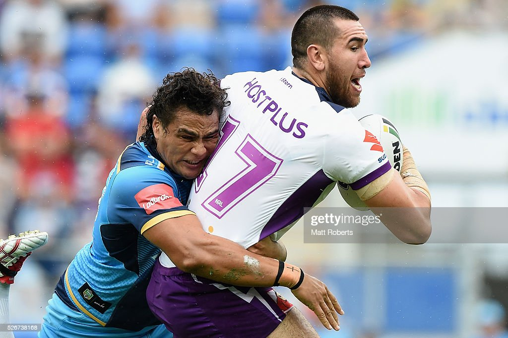 Nelson Asofa-Solomona of the Storm is tackled by Leivaha Pulu of the Titans during the round nine NRL match between the Gold Coast Titans and the Melbourne Storm on May 1, 2016 in Gold Coast, Australia.