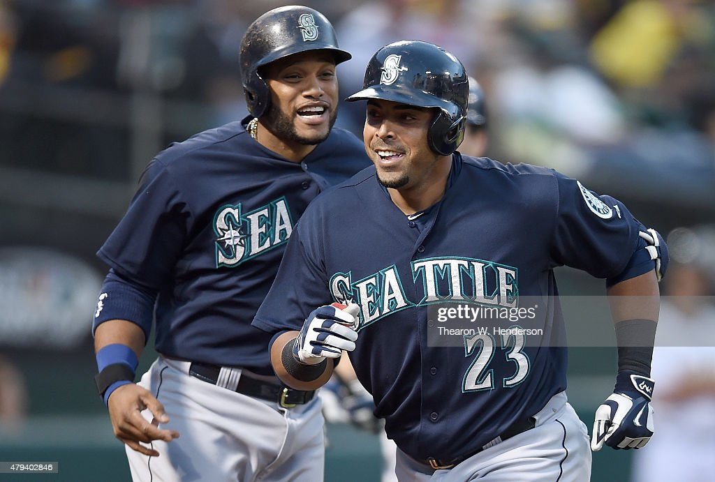 Nelson Cruz #23 and Robinson Cano #22 of the Seattle Mariners celebrates after Cruz hit a two-run homer against the Oakland Athletics in the top of the eighth inning at O.co Coliseum on July 3, 2015 in Oakland, California. The Mariners won the game 9-5.
