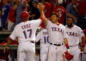 Nelson Cruz Ian Kinsler and Elvis Andrus of the Texas Rangers celebrate after Cruz scored on a tworun double by Mike Napoli in the eighth inning...