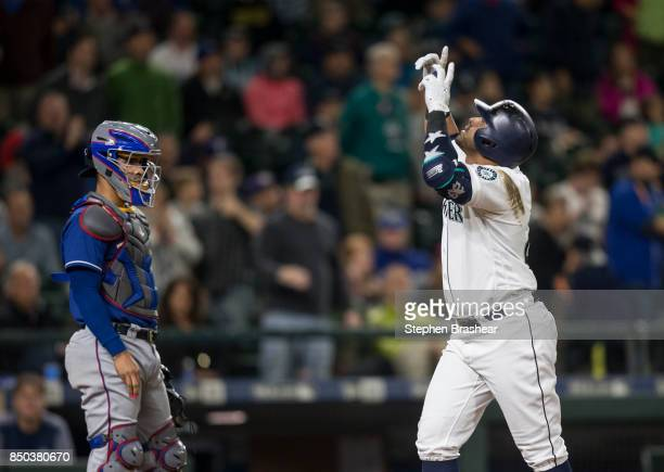 Nelson Cruz of the Seattle Mariners celebrates hitting a solo home run off of starting pitcher Andrew Cashner of the Texas Rangers as he crosses home...