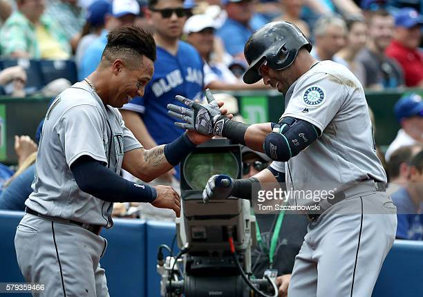 Nelson Cruz of the Seattle Mariners is congratulated by Leonys Martin after hitting a grand slam home run in the third inning during MLB game action...