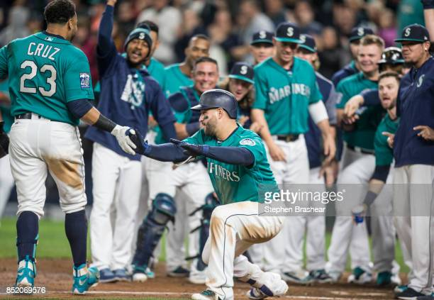 Nelson Cruz of the Seattle Mariners is greeted at home plate by teammates including Yonder Alonso of the Seattle Mariners center after hitting a...