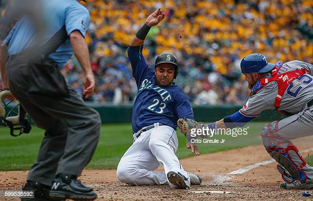 Nelson Cruz of the Seattle Mariners scores on a fielders choice against catcher Jonathan Lucroy of the Texas Rangers in the sixth inning at Safeco...