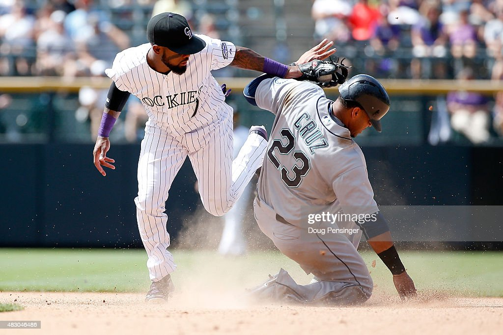 Nelson Cruz #23 of the Seattle Mariners steals second base as shortstop Jose Reyes #7 of the Colorado Rockies makes the late tag in the seventh inning during interleague play at Coors Field on August 5, 2015 in Denver, Colorado. The play was upheld by video review as the Rockies defeated the Mariners 7-5 in 11 innings.