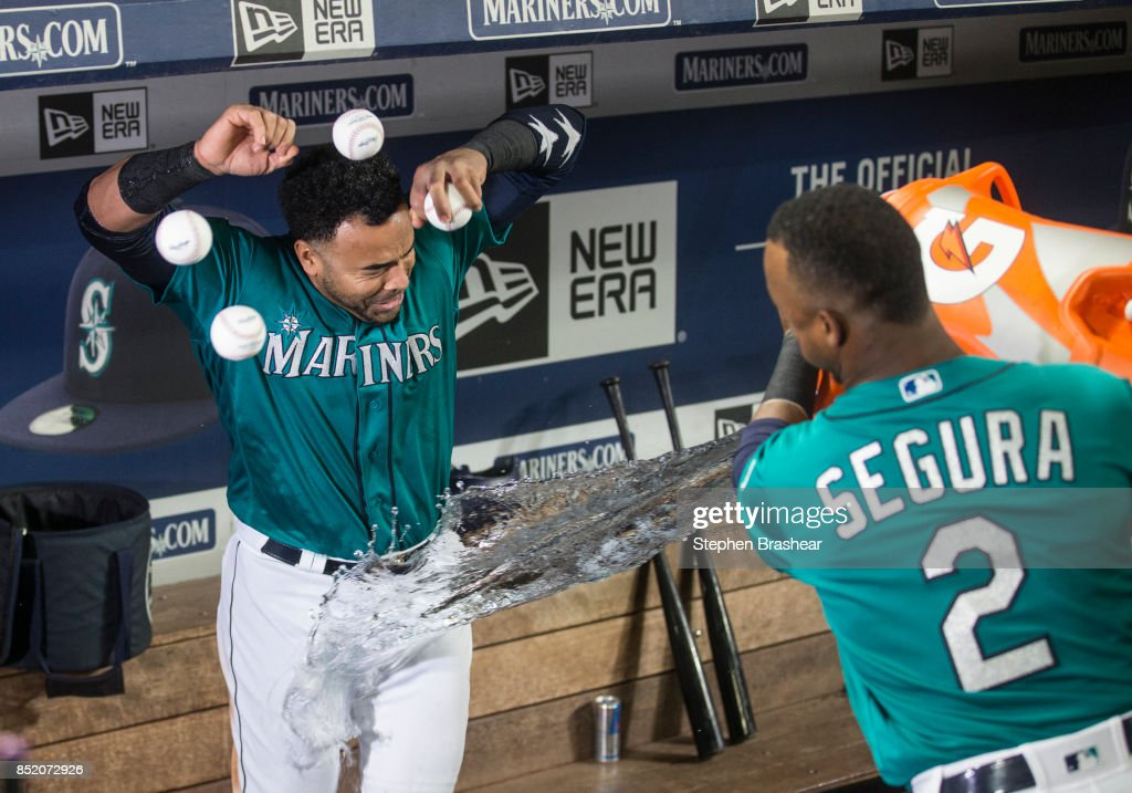 Nelson Cruz #23 of the Seattle Mariners tries avoid a water bath from teammate Jean Segura #2 of the Seattle Mariners after Cruz hit a game-winning two-run home run off of relief pitcher Cody Allen #37 of the Cleveland Indians that also scored Robinson Cano #22 of the Seattle Mariners during the ninth inning of a game at Safeco Field on September 22, 2017 in Seattle, Washington. The Mariners won the game 3-1.