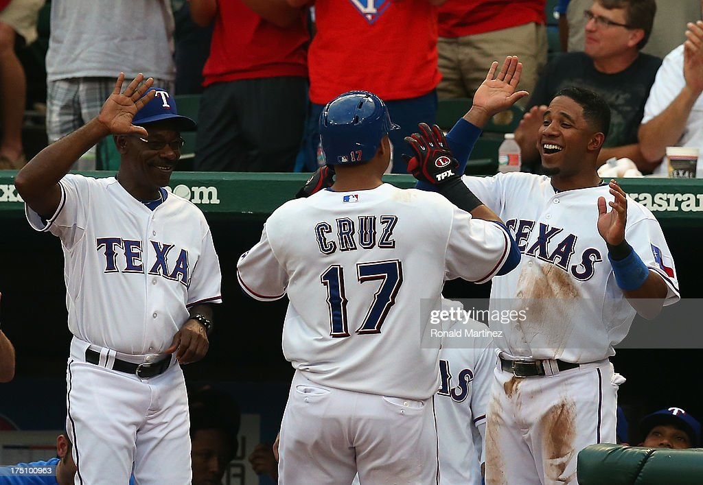 Nelson Cruz #17 of the Texas Rangers celebrates his homerun with Ron Washington and Elvis Andrus against the Los Angeles Angels at Rangers Ballpark in Arlington on July 31, 2013 in Arlington, Texas.