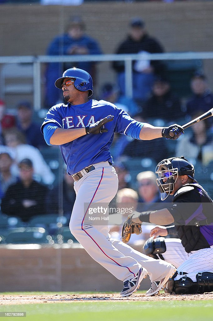 Nelson Cruz #17 of the Texas Rangers follows through on a swing against the Colorado Rockies during a spring training game at Salt River Field on February 25, 2013 in Scottsdale, Arizona.