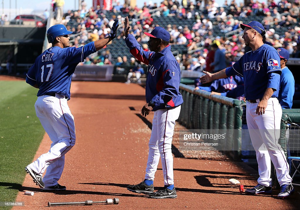 <a gi-track='captionPersonalityLinkClicked' href=/galleries/search?phrase=Nelson+Cruz&family=editorial&specificpeople=235459 ng-click='$event.stopPropagation()'>Nelson Cruz</a> #17 of the Texas Rangers high-fives manager <a gi-track='captionPersonalityLinkClicked' href=/galleries/search?phrase=Ron+Washington&family=editorial&specificpeople=225012 ng-click='$event.stopPropagation()'>Ron Washington</a> after hitting a two-run home run against the Kansas City Royals during the fourth inning of the spring training game at Surprise Stadium on February 22, 2013 in Surprise, Arizona.