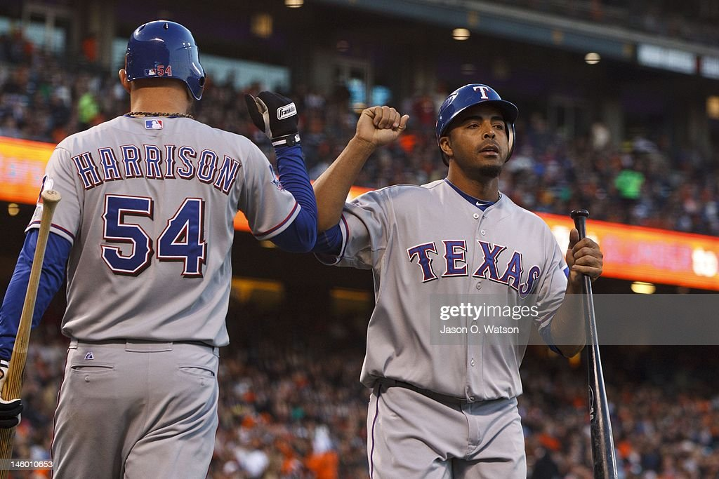Nelson Cruz #17 of the Texas Rangers (right) is congratulated by Matt Harrison #54 after scoring a run against the San Francisco Giants during the fourth inning of an interleague game at AT&T Park on June 8, 2012 in San Francisco, California.