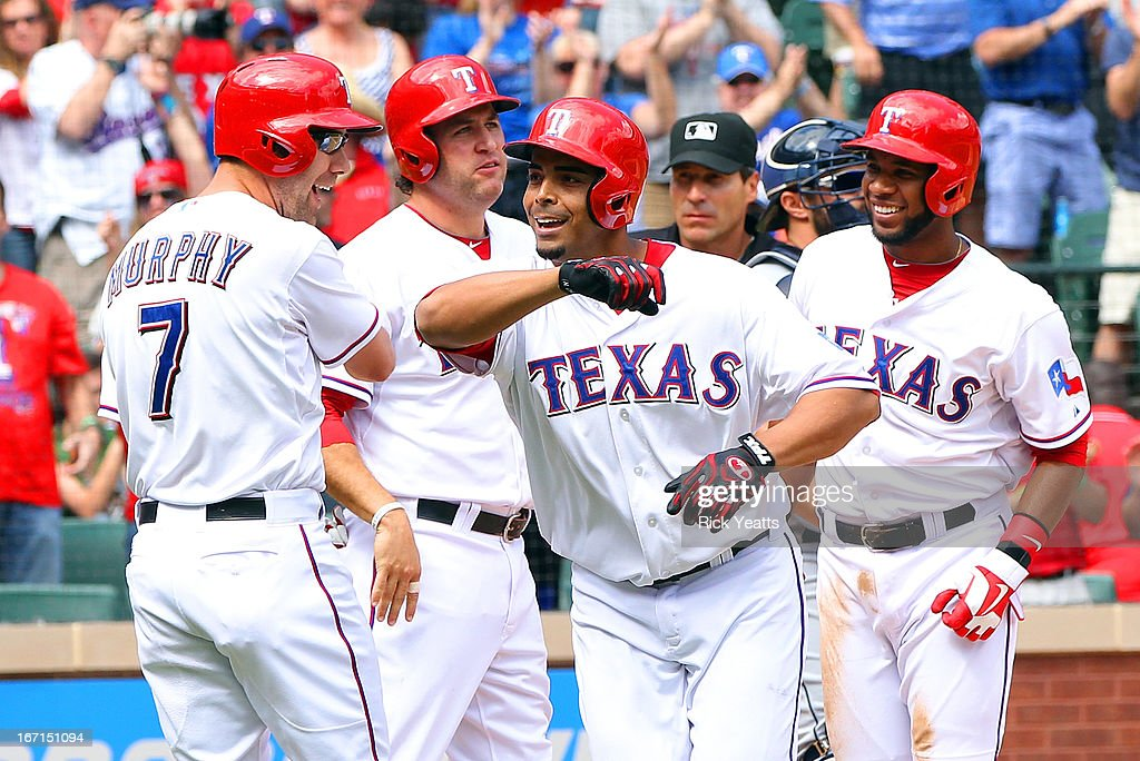 Nelson Cruz #17 of the Texas Rangers is congratulated on grand slam home run bringing in Elvis Andrus #1, David Murphy #7 and Lance Berkman #27 against the Seattle Mariners at Rangers Ballpark in Arlington on April 21, 2013 in Arlington, Texas.