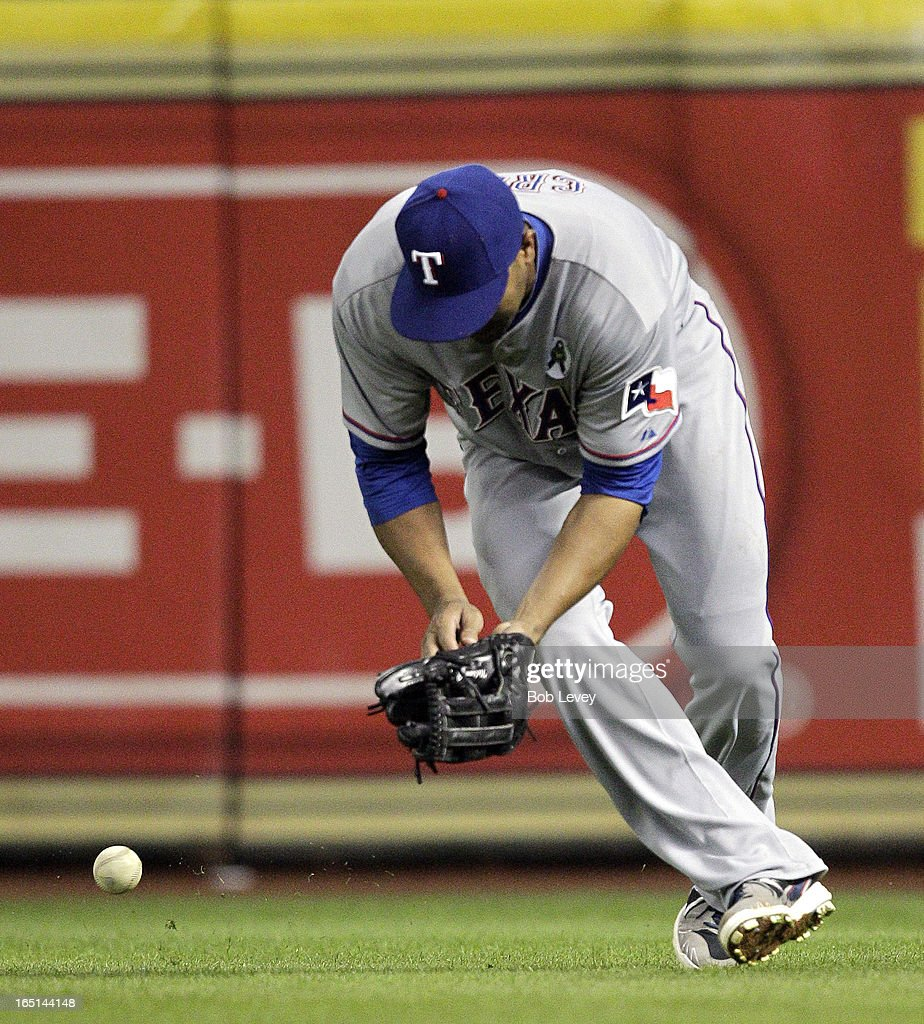 <a gi-track='captionPersonalityLinkClicked' href=/galleries/search?phrase=Nelson+Cruz&family=editorial&specificpeople=235459 ng-click='$event.stopPropagation()'>Nelson Cruz</a> #17 of the Texas Rangers mishandles a line drive by Ronny Cedeno #13 of the Houston Astros in the fifth inning on Opening Day at Minute Maid Park on March 31, 2013 in Houston, Texas.