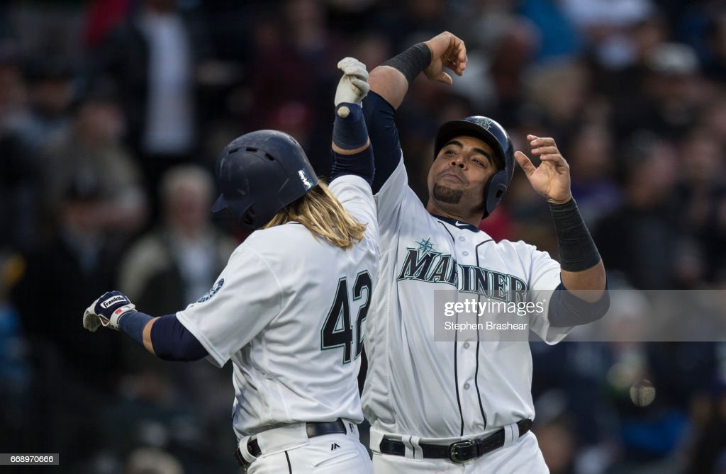 Nelson Cruz #23, right, of the Seattle Mariners congratulates Taylor Motter #21 of the Seattle Mariners after Motter hit a three-run home run off of relieft pitcher Mike Hauschild #49 of the Texas Rangers to score Cruz and Kyle Seager #15 of the Seattle Mariners during the sixth inning of a game at Safeco Field on April 15, 2017 in Seattle, Washington. All players are wearing #42 in honor of Jackie Robinson Day.