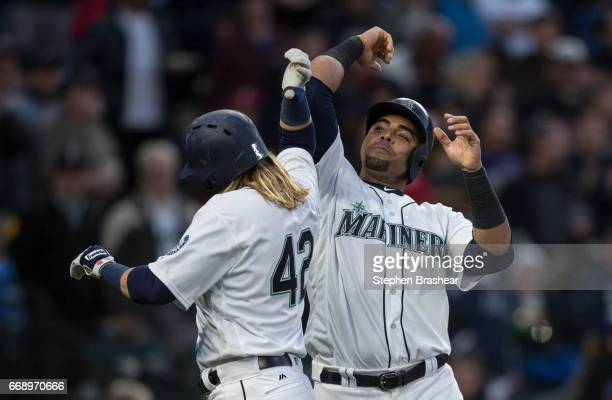 Nelson Cruz right of the Seattle Mariners congratulates Taylor Motter of the Seattle Mariners after Motter hit a threerun home run off of relieft...