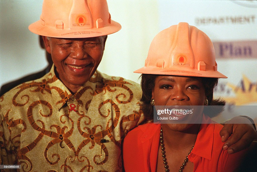 Nelson Mandela has his arm around the shoulders of author and talk show host Oprah Winfrey after they don construction hard hats to break the ground...