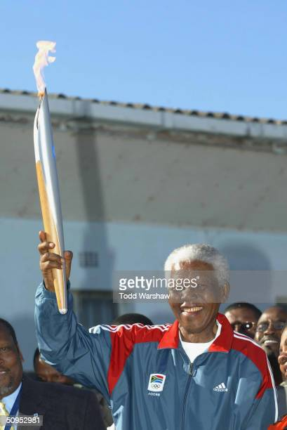 Nelson Mandela holds the Olympic Flame on Robben Island during Day 9 of the ATHENS 2004 Olympic Torch Relay June 12 2004 in Cape Town South Africa...