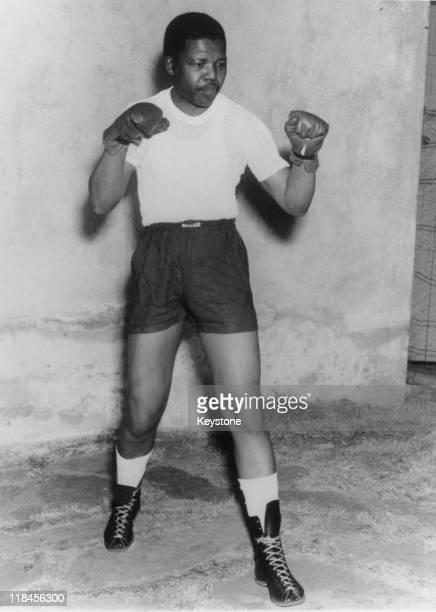 Nelson Mandela leader of the African National Congress adopts a boxing pose wearing shorts tshirt and boxing gloves circa 1950