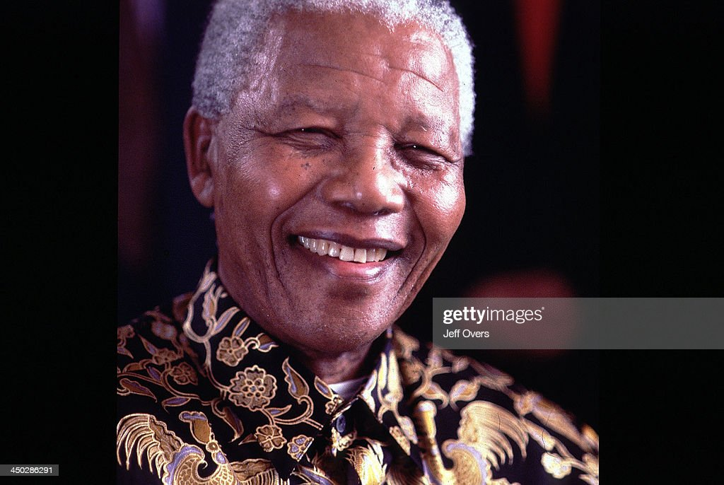 Nelson Mandela wearing a loud shirt and smiling.