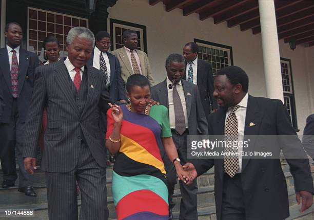 Nelson Mandela Zanele Mbeki Thabo Mbeki and Cyril Ramaphosa walking towards parliament on the day the new constitution was adopted May 1996