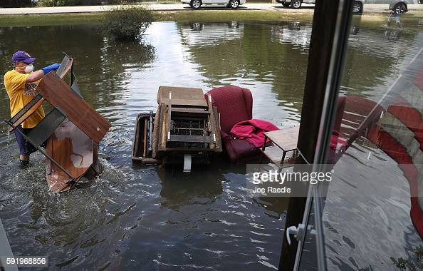 Nelson Morgan jr throws water logged items out as he clears out his father's home after flood waters inundated it on August 19 2016 in St Amant...
