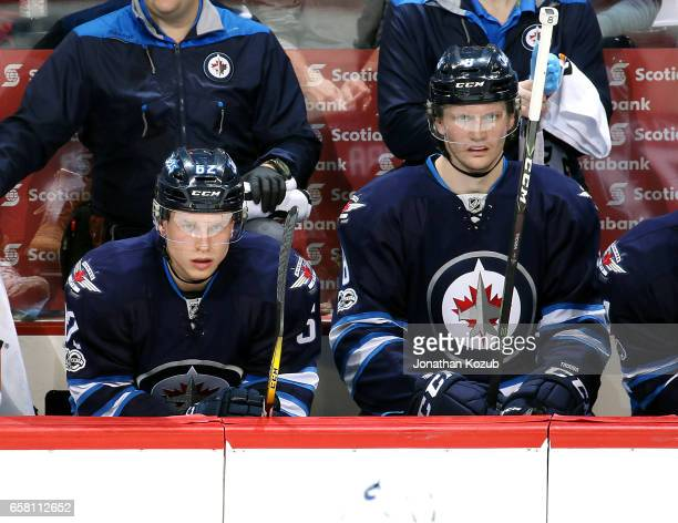 Nelson Nogier and Jacob Trouba of the Winnipeg Jets look on from the bench during second period action against the Vancouver Canucks at the MTS...