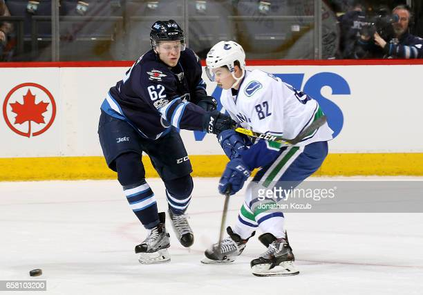 Nelson Nogier of the Winnipeg Jets battles Nikolay Goldobin of the Vancouver Canucks as the puck squirts loose during first period action at the MTS...