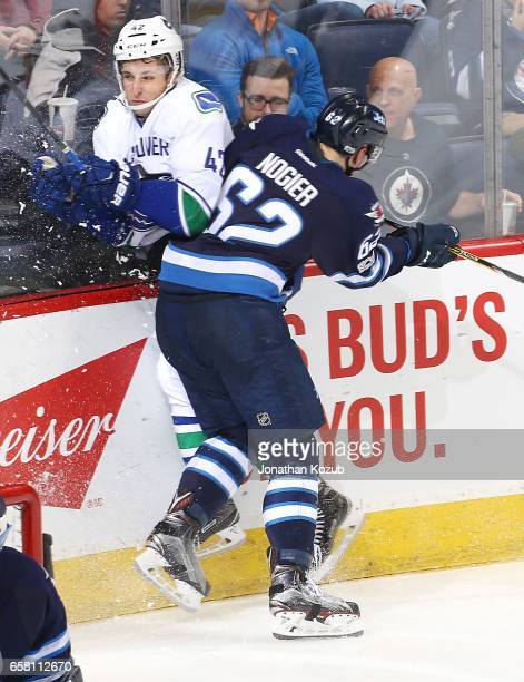 Nelson Nogier of the Winnipeg Jets checks Drew Shore of the Vancouver Canucks along the boards during second period action at the MTS Centre on March...