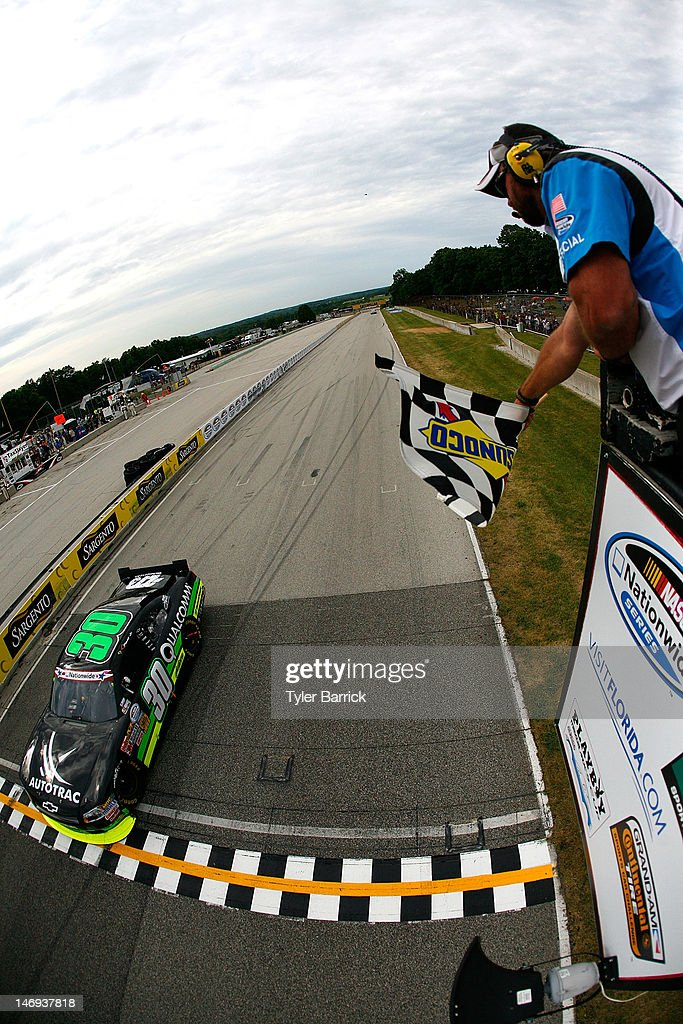 Nelson Piquet Jr driver of the Autotrac Chevrolet crosses the finish line to win the NASCAR Nationwide Series Sargento 200 at Road America on June 23...