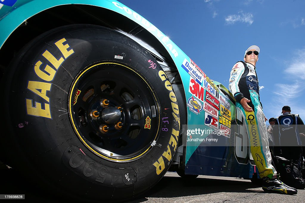 Nelson Piquet Jr., driver of the #30 Qualcomm Chevrolet, leans on his car on the grid during the NASCAR Nationwide Series Zippo 200 at Watkins Glen International on August 10, 2013 in Watkins Glen, New York.