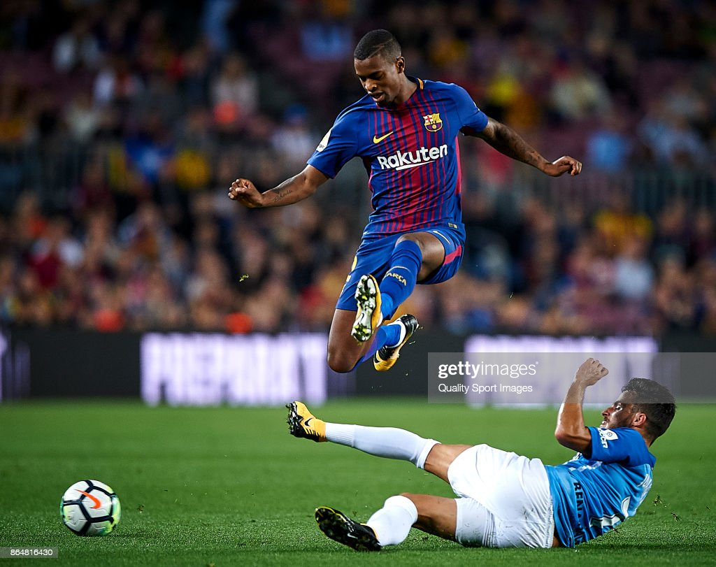 Nelson Semedo (L) of Barcelona competes for the ball with Juankar of Malaga during the La Liga match between Barcelona and Malaga at Camp Nou on October 21, 2017 in Barcelona, Spain.