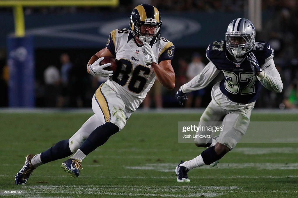 Nelson Spruce #86 of the Los Angeles Rams avoids getting tackled by Jeremiah McKinnon #37 of the Dallas Cowboys during a preseason game at the Los Angeles Memorial Coliseum on August 13, 2016 in Los Angeles, California.