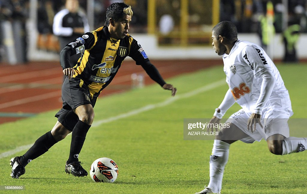 Nelvin Soliz (L) of Bolivia's The Strongest, vies for the ball with Junior Cesar of Brazil's Atletico Mineiro during their Copa Libertadores football match at Hernando Siles stadium in La Paz, Bolivia, on March 13, 2013. AFP PHOTO/Aizar Raldes