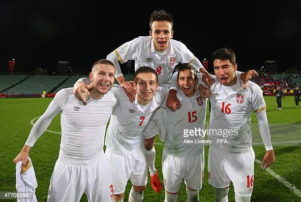 Nemanja Maksimovic of Serbia jumps on the backs of team mates Nemanja Antonov Ivan Saponjic Miladin Stevanovic and Marko Grujic after victory in the...