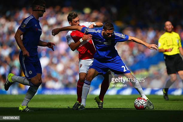 Nemanja Matic of Chelsea and Mesut Ozil of Arsenal compete for the ball during the Barclays Premier League match between Chelsea and Arsenal at...