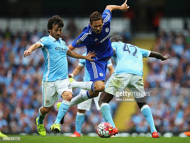 Nemanja Matic of Chelsea is tackled by David Silva and Yaya Toure of Manchester City during the Barclays Premier League match between Manchester City...