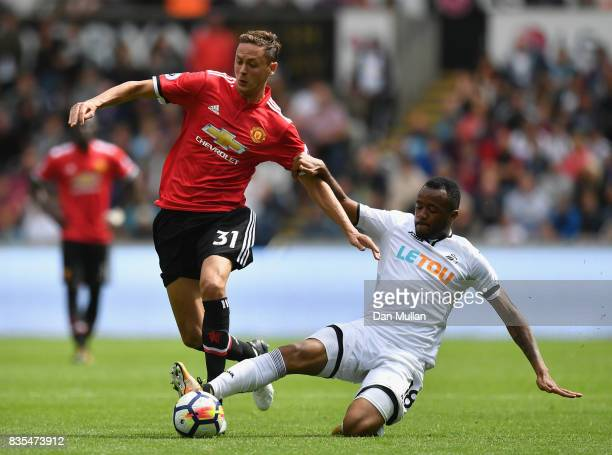 Nemanja Matic of Manchester United and Jordan Ayew of Swansea City battle for posession during the Premier League match between Swansea City and...