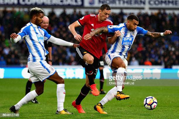 Nemanja Matic of Manchester United battles with Martin Cranie Danny Williams both of Huddersfield Town during the Premier League match between...