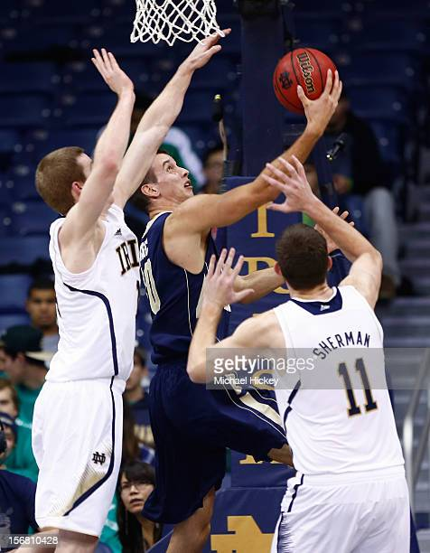 Nemanja Mikic of the George Washington Colonials puts up a layup as Scott Martin of the Notre Dame Fighting Irish and Garrick Sherman of the Notre...