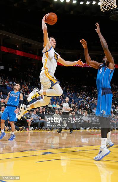 Nemanja Nedovic of the Golden State Warriors goes up for the dunk against Bernard James of the Dallas Mavericks on March 11 2014 at Oracle Arena in...