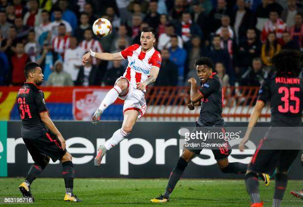 Nemanja Radonjic of Crvena Zvezda in action against Joseph Willock and Francis Coquelin of Arsenal during the UEFA Europa League group H match...