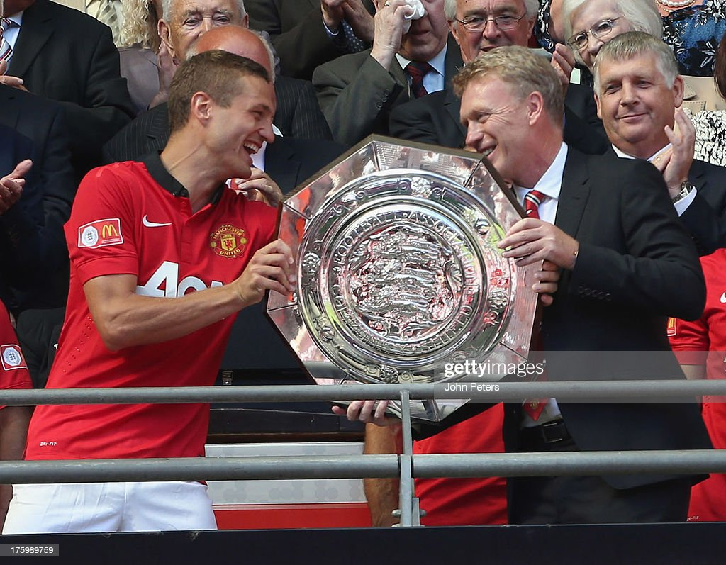 <a gi-track='captionPersonalityLinkClicked' href=/galleries/search?phrase=Nemanja+Vidic&family=editorial&specificpeople=497253 ng-click='$event.stopPropagation()'>Nemanja Vidic</a> and Manager <a gi-track='captionPersonalityLinkClicked' href=/galleries/search?phrase=David+Moyes&family=editorial&specificpeople=215482 ng-click='$event.stopPropagation()'>David Moyes</a> of Manchester United pose with the FA Community Shield trophy after the FA Community Shield match between Manchester United and Wigan Athletic at Wembley Stadium on August 11, 2013 in London, England.
