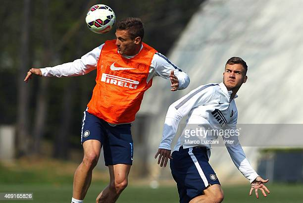 Nemanja Vidic competes with George Puscas during FC Internazionale training session at the club's training ground on April 10 2015 in Appiano Gentile...