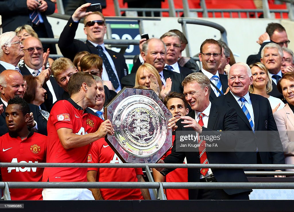 <a gi-track='captionPersonalityLinkClicked' href=/galleries/search?phrase=Nemanja+Vidic&family=editorial&specificpeople=497253 ng-click='$event.stopPropagation()'>Nemanja Vidic</a> of Manchester United and Manager of Manchester United <a gi-track='captionPersonalityLinkClicked' href=/galleries/search?phrase=David+Moyes&family=editorial&specificpeople=215482 ng-click='$event.stopPropagation()'>David Moyes</a> celebrate with the shield during the FA Community Shield match between Manchester United and Wigan Athletic at Wembley Stadium on August 11, 2013 in London, England.