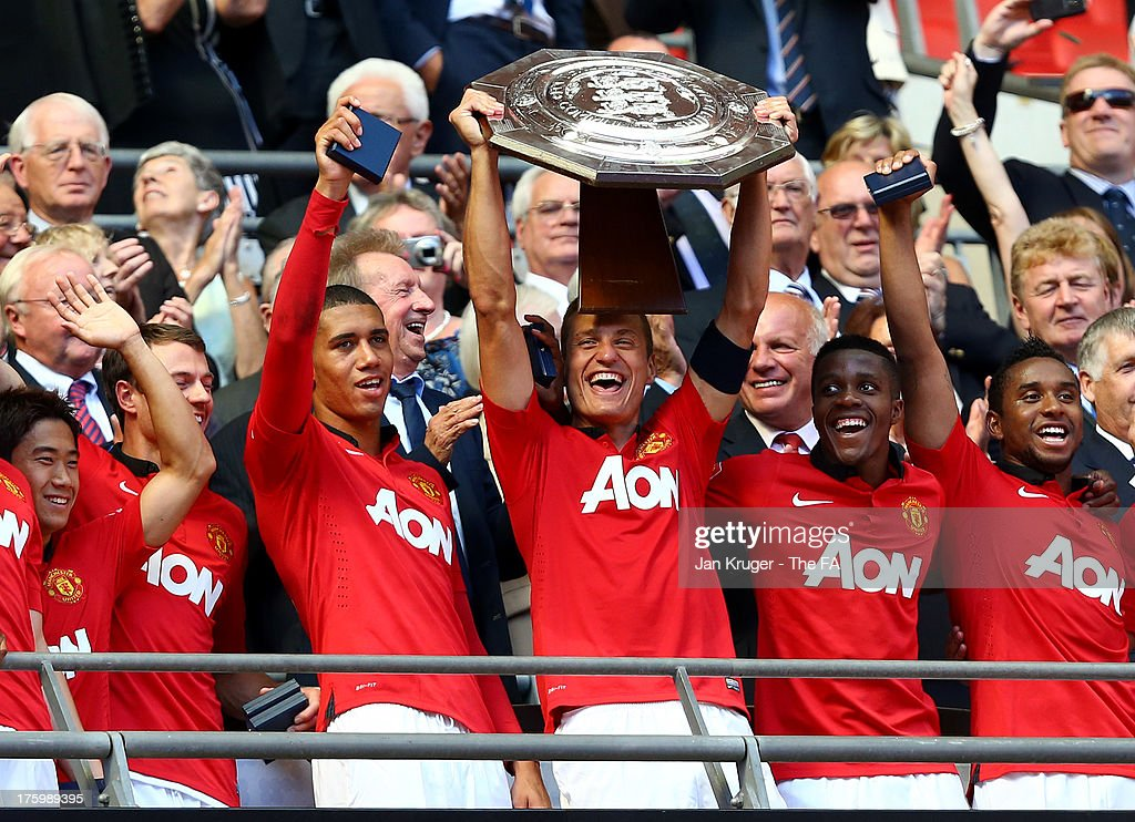 <a gi-track='captionPersonalityLinkClicked' href=/galleries/search?phrase=Nemanja+Vidic&family=editorial&specificpeople=497253 ng-click='$event.stopPropagation()'>Nemanja Vidic</a> of Manchester United and team mates celebrate with the shield during the FA Community Shield match between Manchester United and Wigan Athletic at Wembley Stadium on August 11, 2013 in London, England.