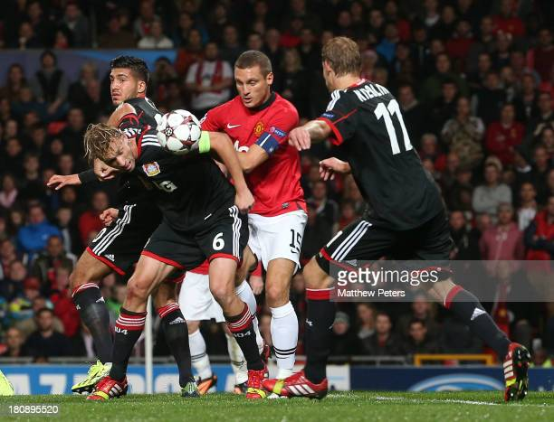 Nemanja Vidic of Manchester United in action with Simon Rolfes and Stefan Kiessling of Bayer Leverkusen during the UEFA Champions League Group A...