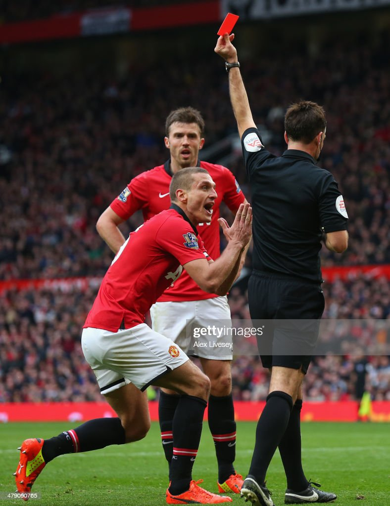 Nemanja Vidic of Manchester United is shown a red card by Referee Mark Clattenburg during the Barclays Premier League match between Manchester United and Liverpool at Old Trafford on March 16, 2014 in Manchester, England.